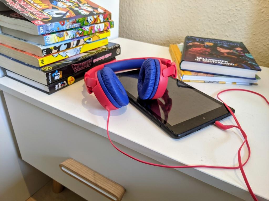 Tablet für Kinder auf dem Nachttisch, neben Comics und Büchern
